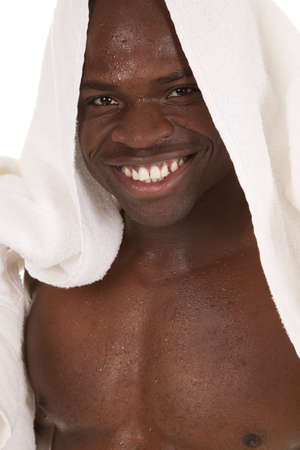 a man with a smile on his head with a towel on his head and water all over his body photo