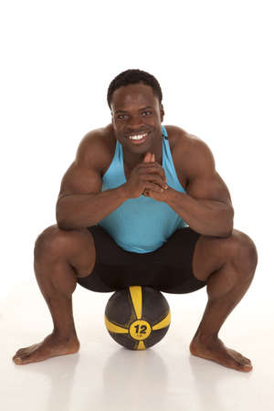 A man sitting on a medicine ball with a smile on his face. photo