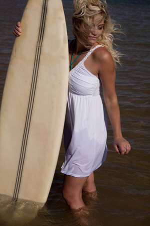 A woman standing in the water holding on to her board looking down at the water with the wind blowing her hair. photo