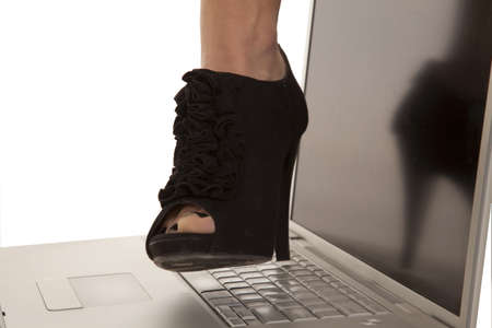 A womans foot getting ready to step oh the keyboard of the laptop photo