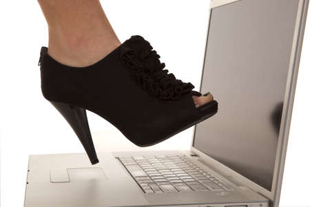 a woman getting ready to step on the computer with her shoes. photo