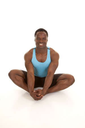 A man sitting and stretching out his legs with a smile on his face.