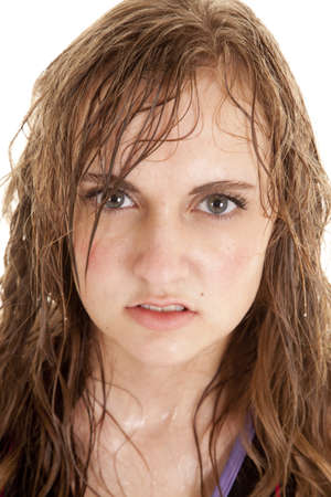 A woman has wet sweaty hair and face with a serious expression.