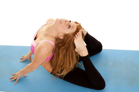 a top view of a woman touching her head with her feet stretching.  photo