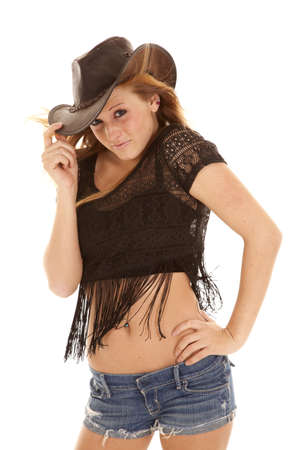 a beautiful woman hanging on to her cowboy hat with a small smile on her face.