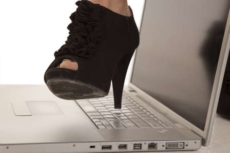 A woman getting ready to crush her laptop with her heel photo