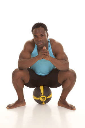 A man with a serious expression on his face sitting on a medicine ball. photo