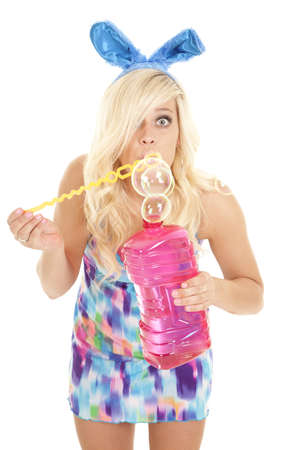 A woman dressed like a bunny blowing bubbles. photo