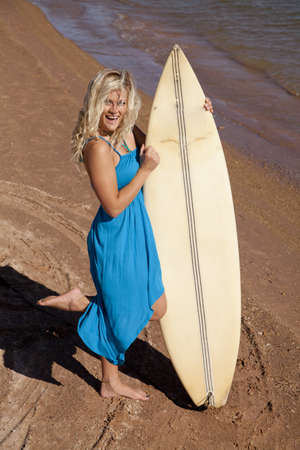 A woman with a big smile on her face holding on to her surf board. photo