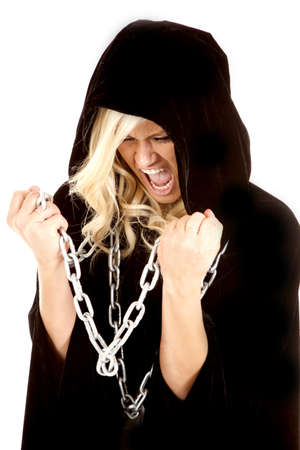 A woman holding on to a chain while wearing her black cape yelling. photo