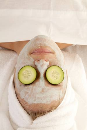 A top view of a woman in the spa with cucumbers on her eyes. photo