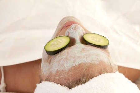 A woman with cucumber on her eyes laying down.