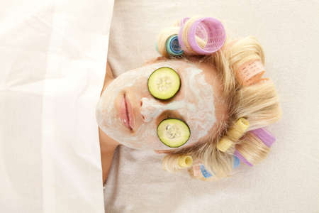 A woman is laying with curlers and a cream face mask.