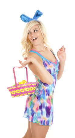 A woman with an easter basket and ears looks back. photo