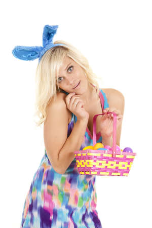 A woman with an easter basket looks forward and smiles. photo