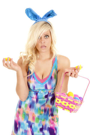 A woman is holding an open easter egg and a basket of easter eggs.  She has a surprised expression on her face.  photo