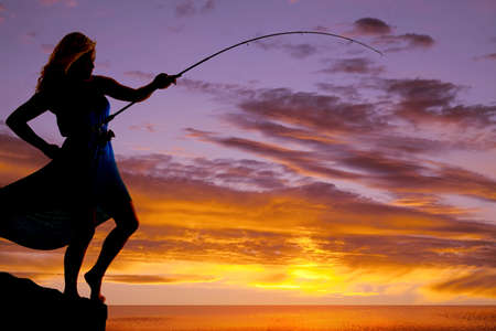 A woman is silhouetted in the sunset with a fishing pole bent to the water.