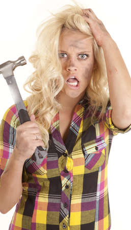 frazzled: A woman is holding a hammer in her hand and looks very frustrated. Stock Photo