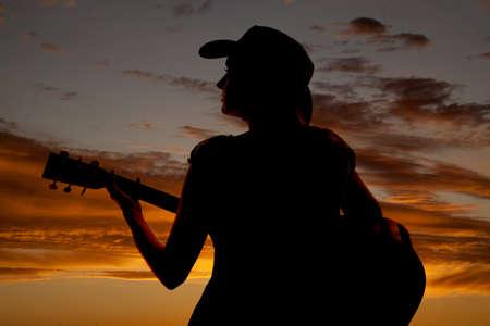 femme avec guitare: Une femme est assise avec une guitare dans le coucher du soleil.
