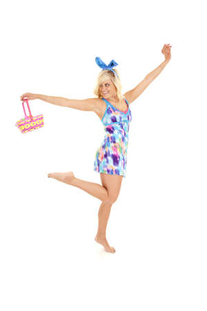 A woman is very happy.  She is dressed like an easter bunny with a basket of eggs. photo