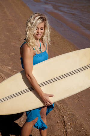 A woman holding on to her surf board walking with a small smile on her lips photo