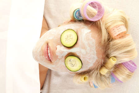 hair roller: A woman laying down with curlers in her hair and a cream face mask. Stock Photo
