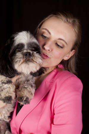 puckered lips: A woman with her lips puckered getting ready to kiss her dog. Stock Photo