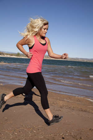 A woman is running on the shorline by the water. photo