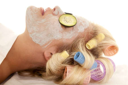 A woman with curlers in her hair and a face mask with cucumbers. photo