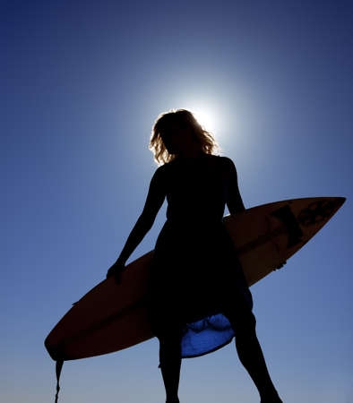 A silhouette of a woman holding her surf board with the blue sky and sun shining on her. photo