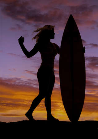 A woman is standing by her surf board silhouetted in the sunset.  photo
