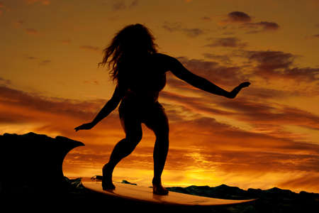 A woman is on a surfboard in the water at sunset. photo