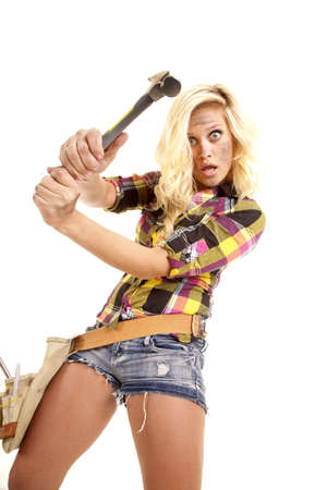 A woman is swinging a hammer.  She is in shorts and a plaid shirt. photo
