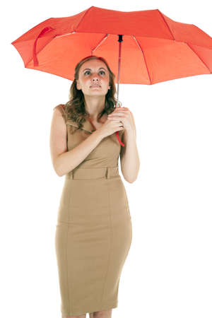 A woman standing under a red umbrella with a small smile on her lips. photo