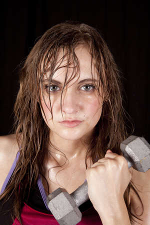 A woman is looking and sweating and holding a weight.