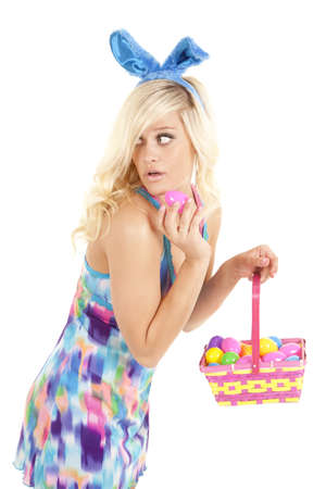 A woman holding a basket of easter eggs looks back as if getting caught. photo