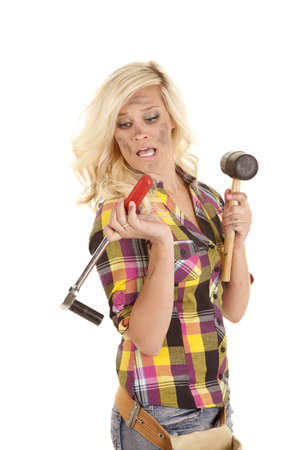 A woman with a rubber mallet and a socket looks scared. photo
