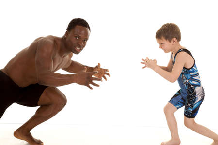 A man with a serious expression on his face getting ready to wrestle the boy. photo