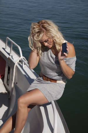 A woman is sitting on the edge of a boat with a phone and looks upset. photo