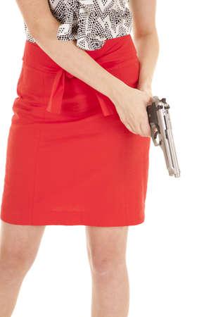 A woman in a red skirt holding a gun.