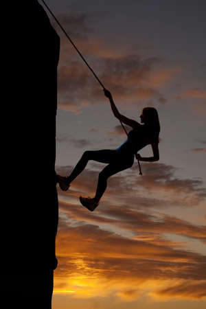 A silhouette of a woman rock climbing with a beautiful sky behind her.