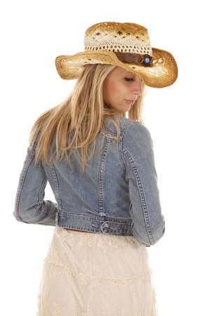 cowgirl hat: Una mujer en su sombrero de vaquera y chaqueta de jean mirando sobre su hombro.