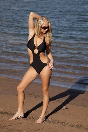 wet suit: A woman in her black swim suit standing on the beach by the water looking down at the sand with her sunglasses on . Stock Photo