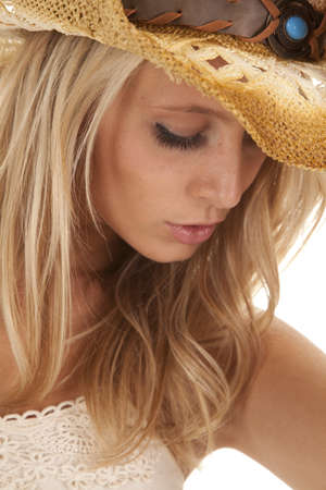A close up of a womans face with her cowgirl hat on and a serious expression on her face. photo