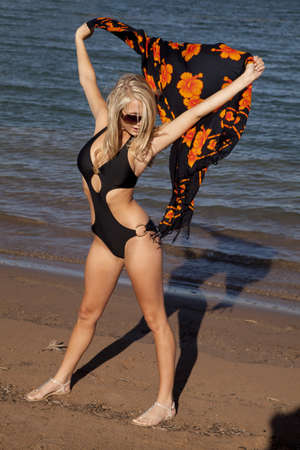 sarong: a woman in her swim suit standing on the beach holding up her orange and black sarong.