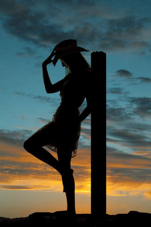 A silhouette of a cowgirl leaning back on a post holding onto her hat with a colorful sky behind her. photo