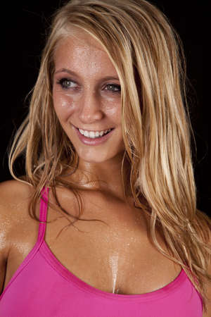 A close up of a womans face with a smile on her face with sweat running off of her face. photo