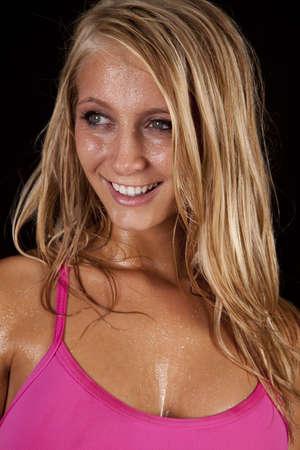 sudando: Un primer plano de la cara de una mujer con una sonrisa en su rostro por el sudor corriendo de su cara.