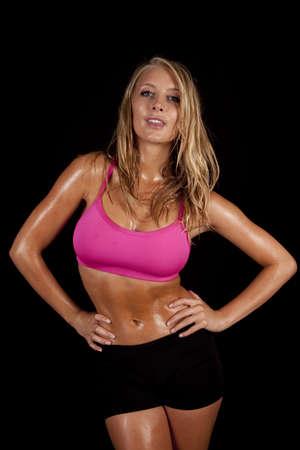 sudoroso: Una mujer con sus manos en sus caderas con una sonrisa en su rostro por el sudor que gotea de su cuerpo.