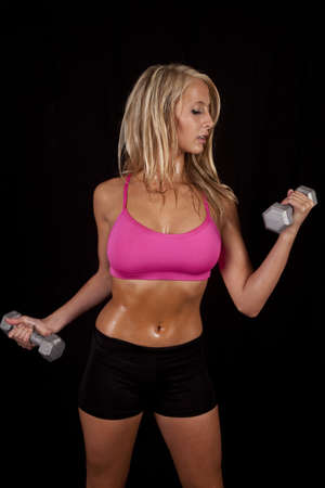 A woman working out with weights on a black background with a sweaty body.
